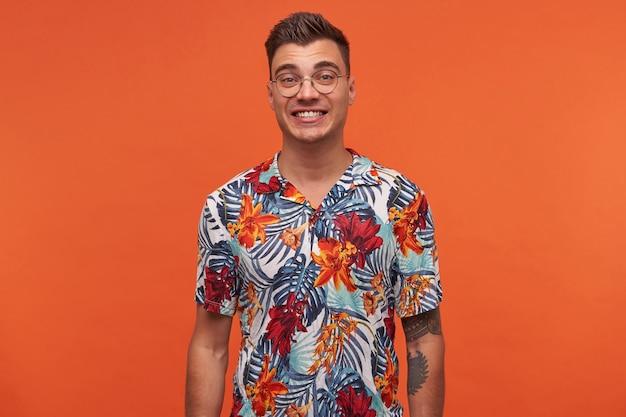 꽃이 만발한 셔츠에 젊은 매력적인 쾌활한 남자가 행복해 보이고, 오렌지 배경 위에 서서 카메라를보고 광범위하게 웃고 있습니다.