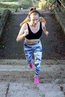 Молодая привлекательная жизнерадостная спортивная девушка бежит вверх по лестнице и слушает музыку.