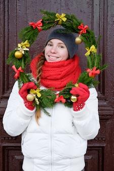 ドアの前にクリスマスリースを保持し、笑顔の赤い手袋と白いジャケットの若い魅力的な陽気な女性