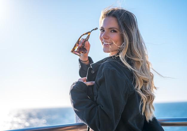 Giovane donna colombiana attraente con occhiali da sole in posa mentre si trova in riva al mare durante il giorno