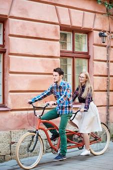 若い魅力的なカップル、ひげを生やした男、サイクリング金髪女性の笑みを浮かべて
