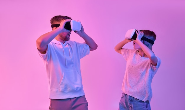 Young attractive couple in casual clothes look at each other in surprise using virtual reality glasses
