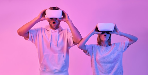 Young attractive couple in casual clothes look surprised using virtual reality glasses