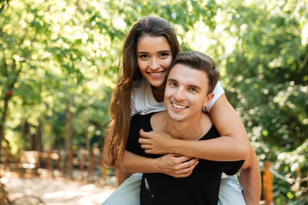 Young attractive couple enjoying piggyback ride