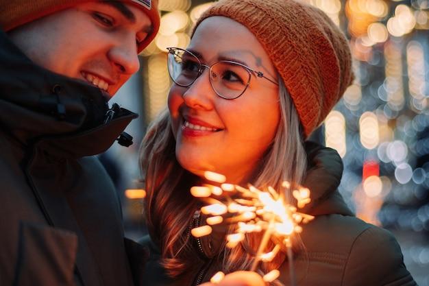 若い魅力的なカップルは、新年を祝う線香花火を手に屋外で抱き合ったりキスしたりします