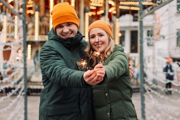 若い魅力的なカップルは、新年を祝う彼らの手で輝きを持って屋外で抱き合ってキスします