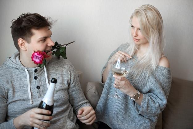 빨간 장미와 와인 병 유리와 사랑에 젊은 매력적인 커플
