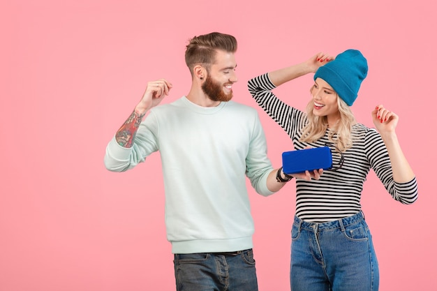 Young attractive couple listening to music on wireless speaker wearing cool stylish outfit smiling happy positive mood posing on pink background isolated dancing having fun