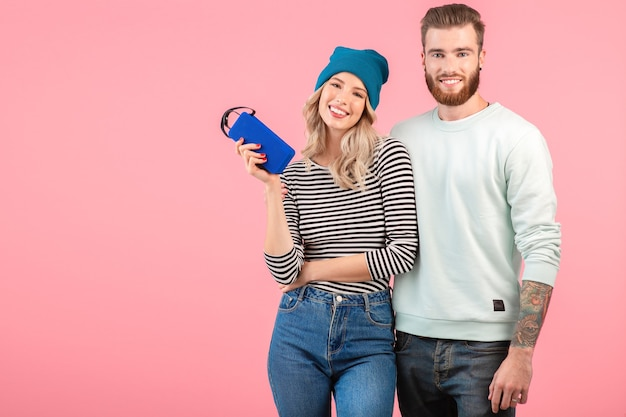 Young attractive couple listening to music on wireless speaker wearing cool stylish outfit smiling happy positive mood posing on pink background