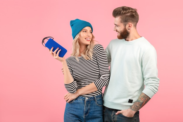Young attractive couple listening to music on wireless speaker wearing cool stylish outfit