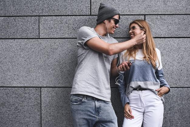 灰色の壁を背景にスタイリッシュな服を着て、同じヘッドフォンで音楽を聴いている若い魅力的なカップル。