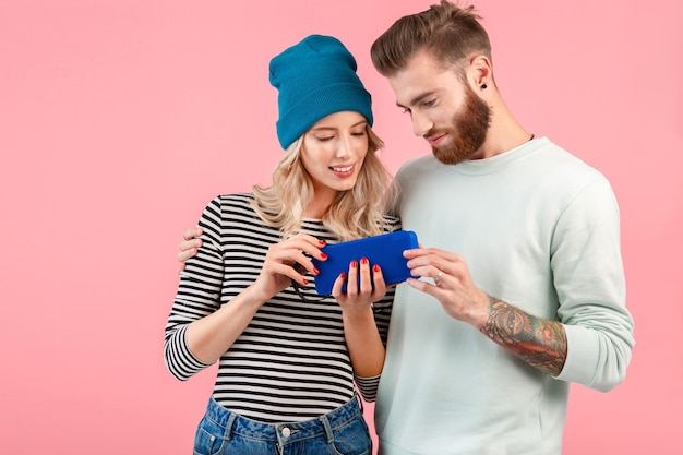 Молодая привлекательная пара слушает музыку на беспроводной колонке, одетая в крутой стильный наряд, улыбаясь, счастливое позитивное настроение, позирует на розовом фоне
