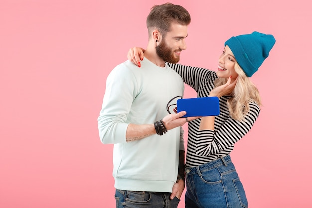 ピンクの背景にポーズをとって幸せなポジティブな気分に笑みを浮かべてクールなスタイリッシュな衣装を着たワイヤレススピーカーで音楽を聴く若い魅力的なカップル