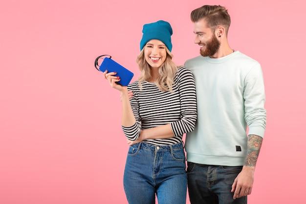 Молодая привлекательная пара слушает музыку на беспроводной колонке, одетая в крутой стильный наряд, улыбаясь, счастливое позитивное настроение, позирует на розовой стене изолированы