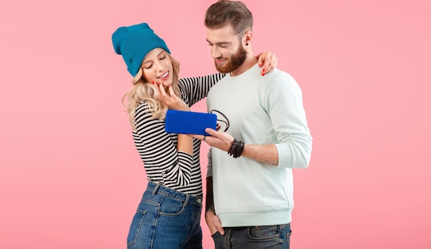 ピンクでポーズをとって幸せな前向きな気分を笑顔クールなスタイリッシュな衣装を着てワイヤレススピーカーで音楽を聴いている若い魅力的なカップル