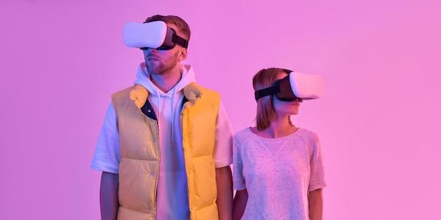 カジュアルな服を着て、手をつないで、仮想現実のメガネを使用して若い魅力的なカップルの男性と女性