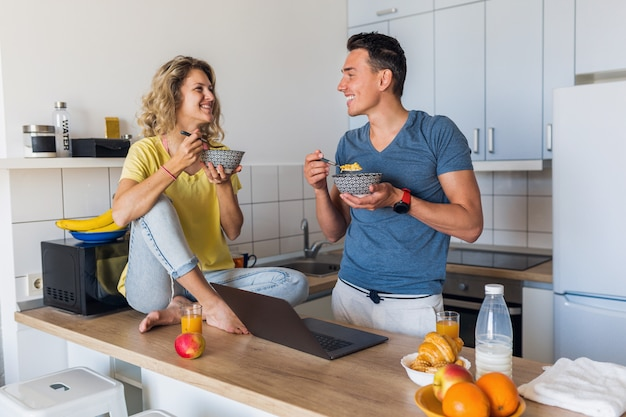 Young attractive couple of man and woman eating breakfast together in morning at kitchen