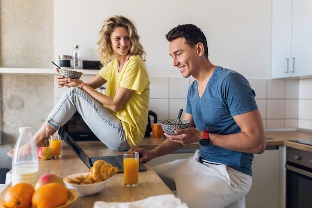 男と女のキッチンで朝一緒に朝食を食べることの若い魅力的なカップル
