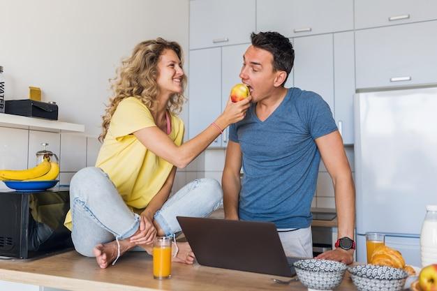 キッチンで朝に一緒に健康的な朝食を食べる男性と女性の若い魅力的なカップル
