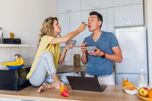 男と女の若い魅力的なカップルは、キッチンで朝一緒に朝食を食べて一緒に一人で家に滞在します。
