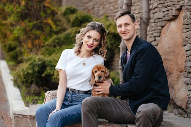 Молодая привлекательная пара играет со своей собакой