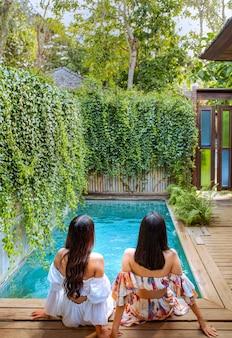 Giovane coppia attraente che si rilassa a bordo piscina in un giardino tropicale