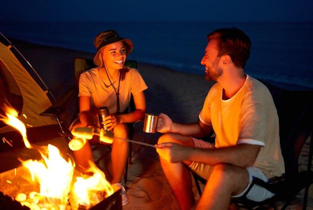 若い魅力的なカップルは、テントの近くの折りたたみ椅子に座って、火でトウモロコシを焼き、お茶を飲み、海の近くで夜に話を楽しんでいます。