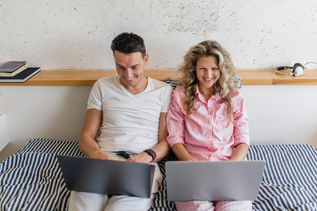 Young attractive couple sitting on bed in morning, man and woman holding laptop