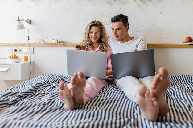 Giovani coppie attraenti che si siedono sul letto la mattina che lavorano in linea