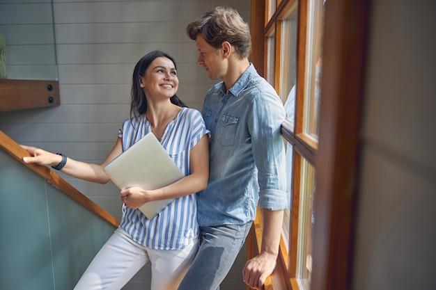 파노라마 창에 서서 서로 웃고있는 젊은 매력적인 부부