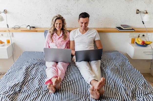 若い魅力的なカップルは朝のベッドに座って一人で一緒に家に滞在します。