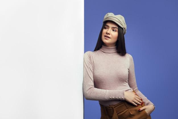 Молодая привлекательная милая девушка, стоящая рядом с пустой белой стеной рекламного щита