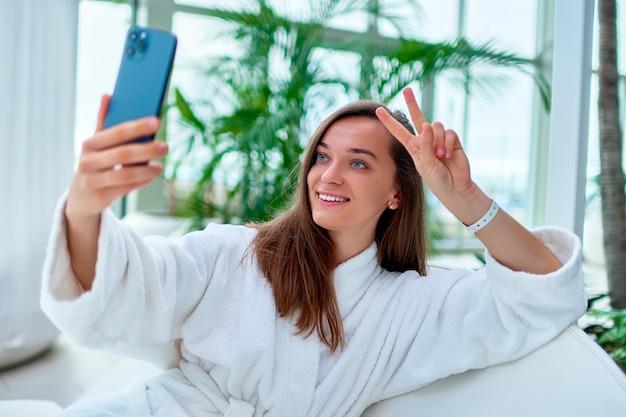 Молодая привлекательная милая улыбающаяся женщина в белом халате, показывающая знак мира двумя пальцами, делающая селфи портретную фотографию на камеру телефона во время отдыха на спа-курорте