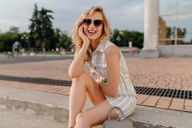 Young attractive cute stylish blonde woman sitting in city street in summer fashion style white cotton dress wearing sunglasses