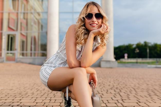 Молодая привлекательная милая стильная блондинка сидит на городской улице в белом хлопковом платье в стиле летней моды в солнцезащитных очках