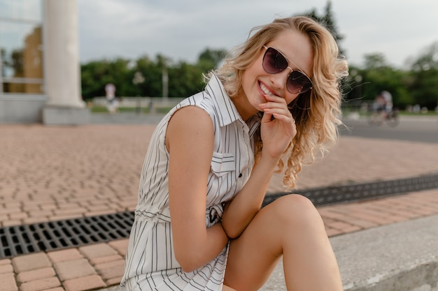 선글라스를 착용하는 여름 패션 스타일 화이트 코튼 드레스에 도시 거리에 앉아 젊은 매력적인 귀여운 세련된 금발의 여자