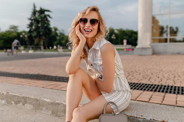 サングラスをかけて夏のファッションスタイルの白い綿のドレスで街の通りに座っている若い魅力的なかわいいスタイリッシュなブロンドの女性 無料写真