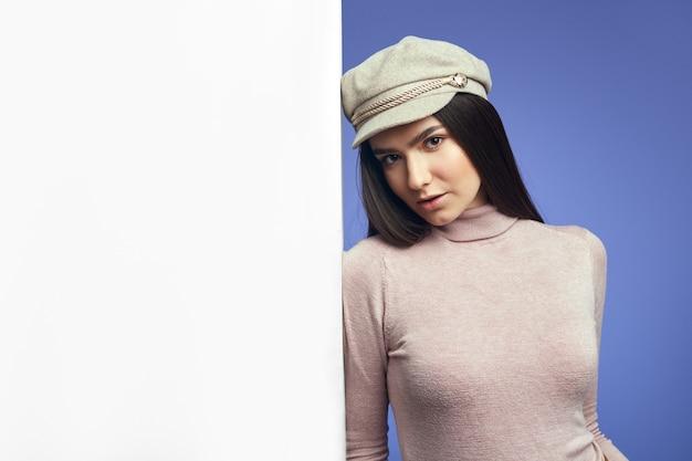Молодая привлекательная милая молодая женщина, стоящая рядом с пустой белой стеной рекламного щита