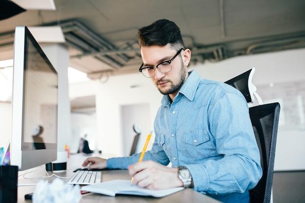 眼鏡の若い魅力的な暗い髪の男はコンピューターで作業して、オフィスでノートに書いています。彼は青いシャツ、ひげを着ています。