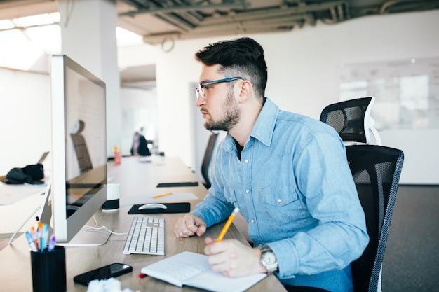 Молодой привлекательный темноволосый мужчина в очках работает с компьютером на своем рабочем месте в офисе. он носит синюю рубашку. он выглядит занятым, вид со стороны.