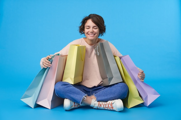 買い物袋がたくさんある短い散髪の若い魅力的な黒髪の女性