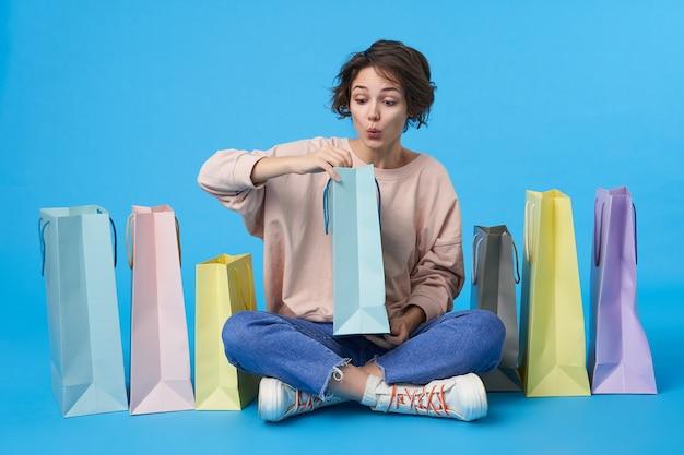 쇼핑백이 많은 짧은 머리를 가진 젊은 매력적인 검은 머리 여자