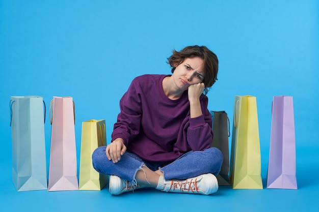 Young attractive dark haired woman with short haircut with a lot of shopping bags