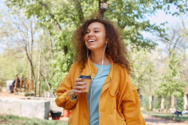 Giovane ragazza riccia dalla pelle scura attraente che sorride ampiamente, camminando nel parco e godersi il tempo, tenendo in mano una tazza di caffè, indossando una giacca gialla, ascoltando musica.