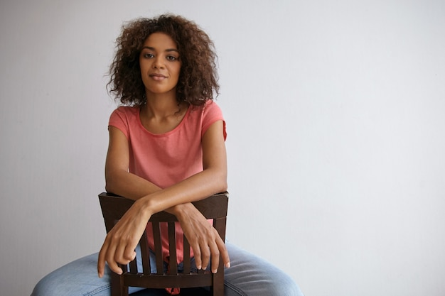 Young attractive dark skinned curly woman looking with calm face and pleasant smile, leaning on chair back with crossed hands