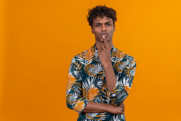 A young attractive dark-skinned man with curly hair in leaves printed shirt thinking while keeping hand on chin