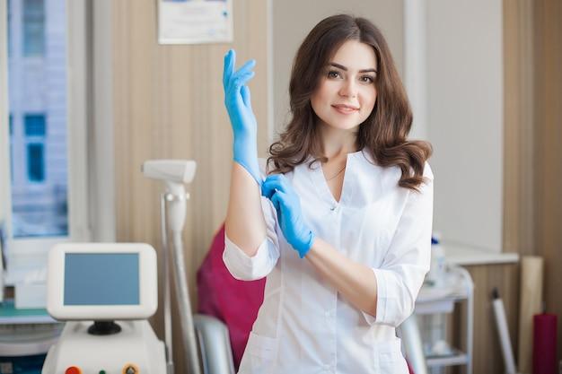 Молодая привлекательная женщина доктора внутри помещения. портрет женщины нося медицинскую форму в клинике. доктор с медицинским оборудованием. косметолог в ее салоне