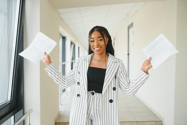 Молодая привлекательная элегантная афро-американская бизнес-леди в формальной одежде в офисном зале.