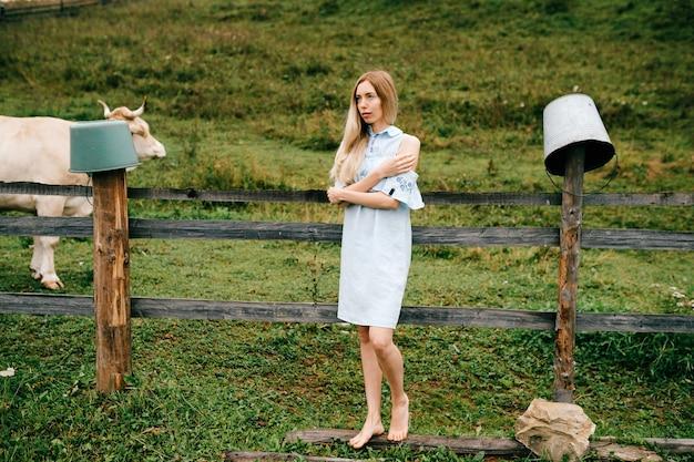 시골에서 포즈를 취하는 파란 드레스에 젊은 매력적인 우아한 금발 소녀