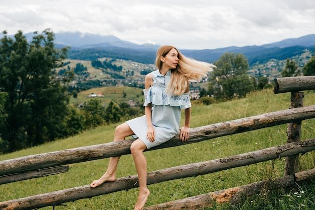 시골에서 나무 울타리에 앉아 블루 로맨틱 드레스에 젊은 매력적인 우아한 금발 소녀